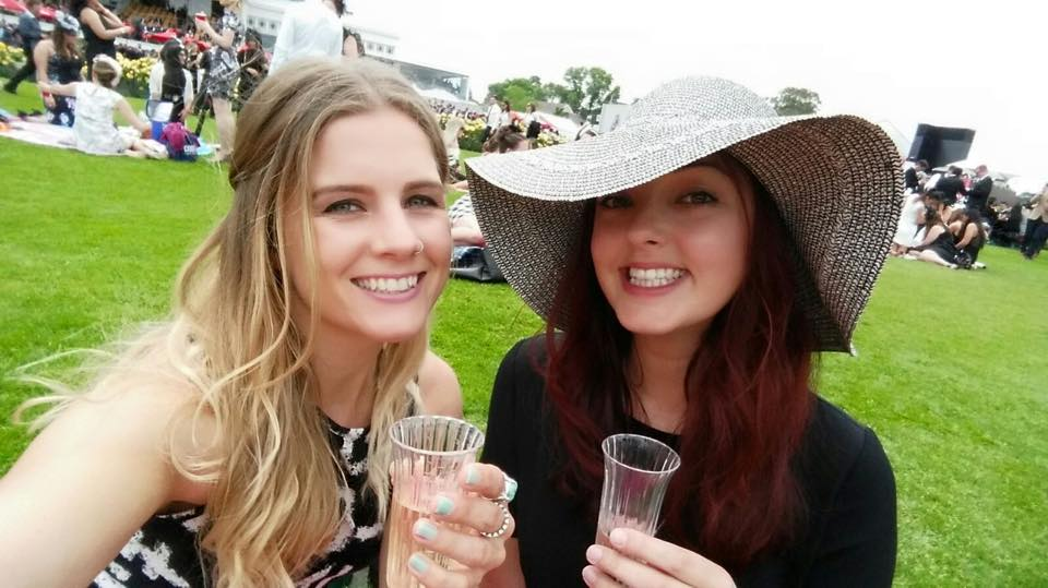 Amy and I smile with our glasses of champagne overlooking the track at Flemington Racecourse