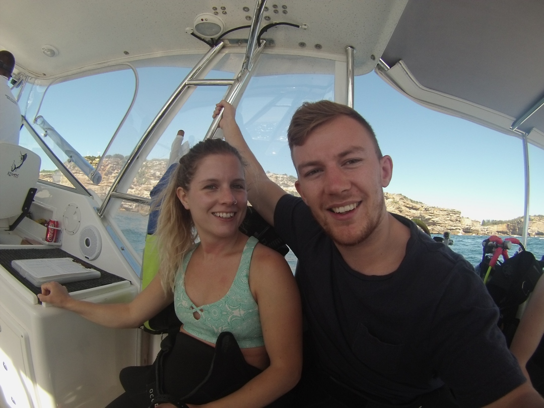 two people smile for the camera while on a boat ride