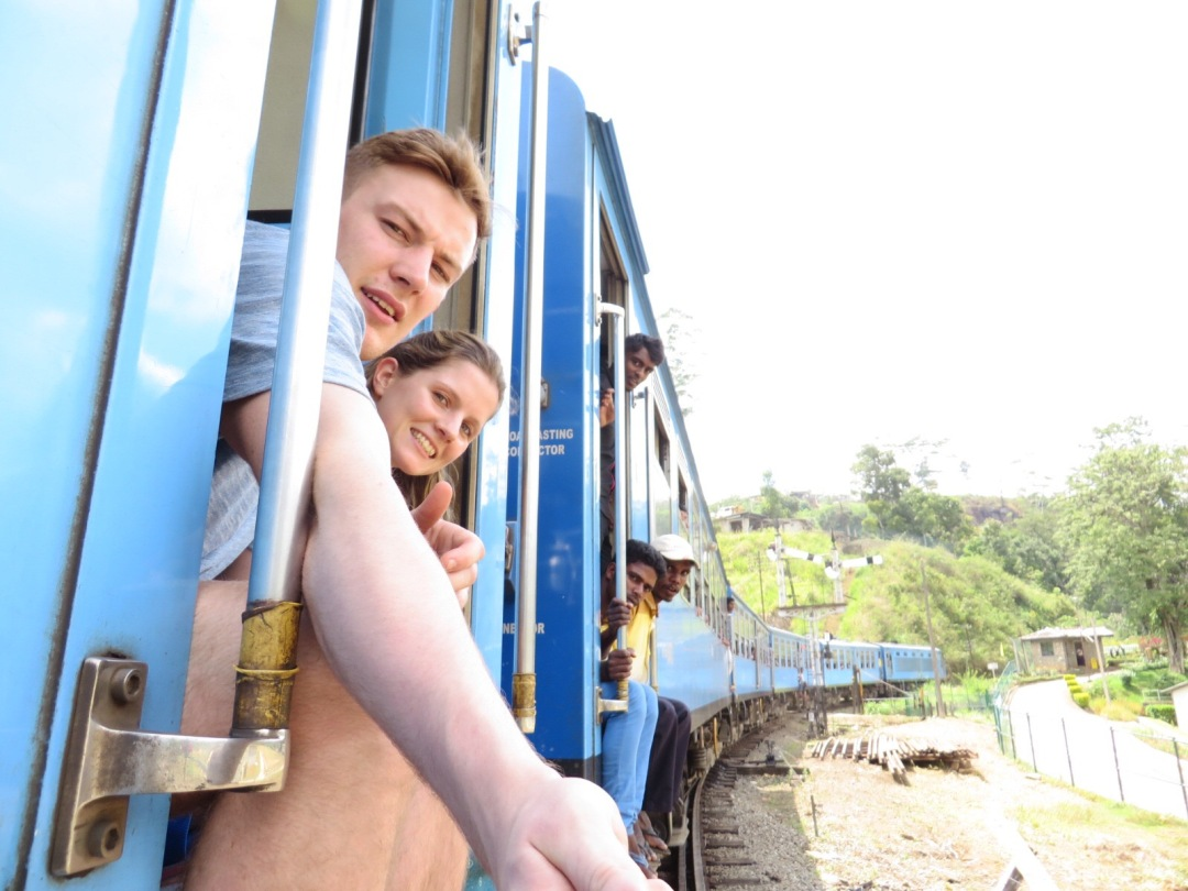 two travellers sit in the doorway of a moving train in Sri Lanka