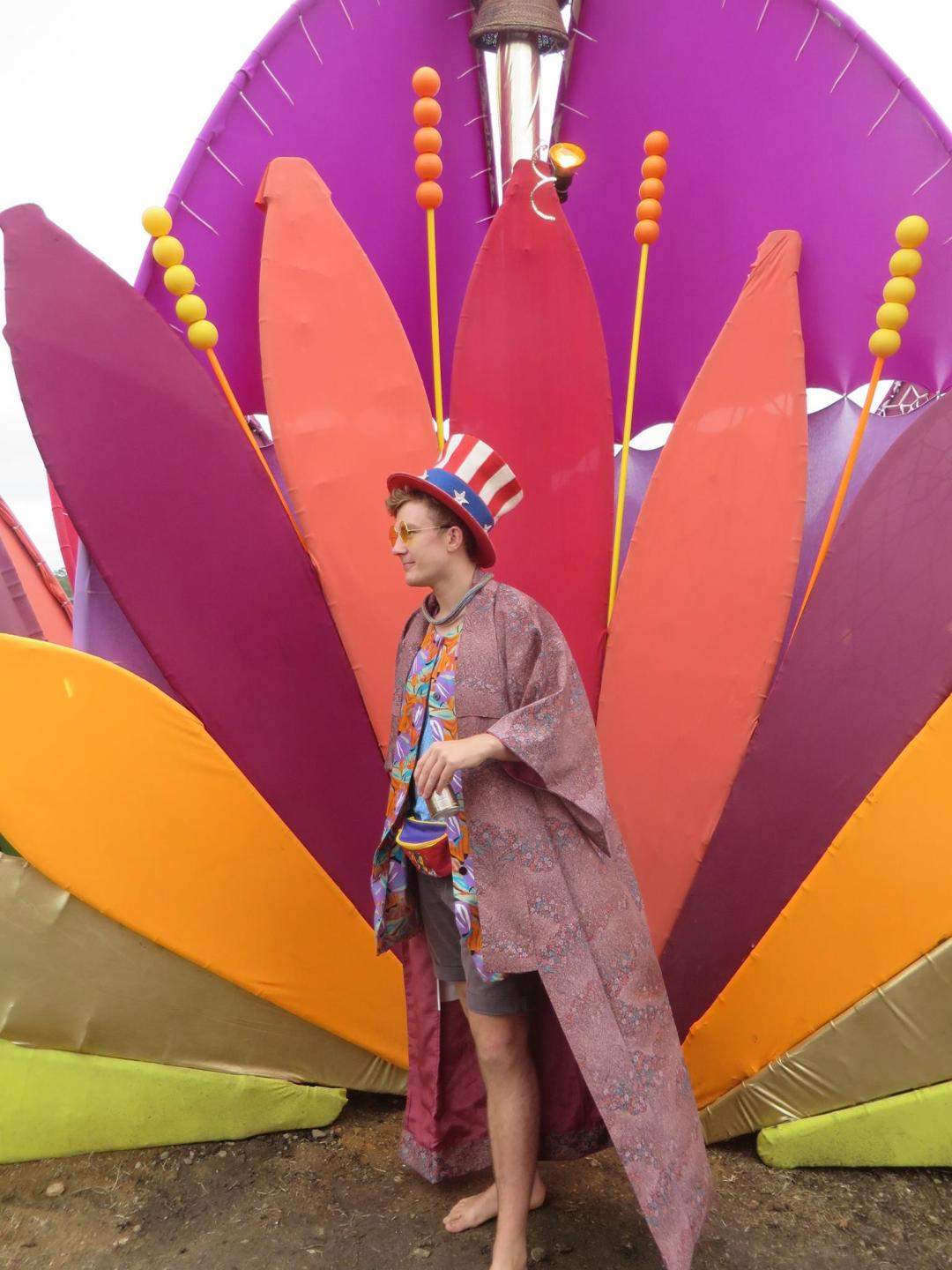 a festival goer stands in fancy dress in front of a giant coloured flower at rainbow serpent festival