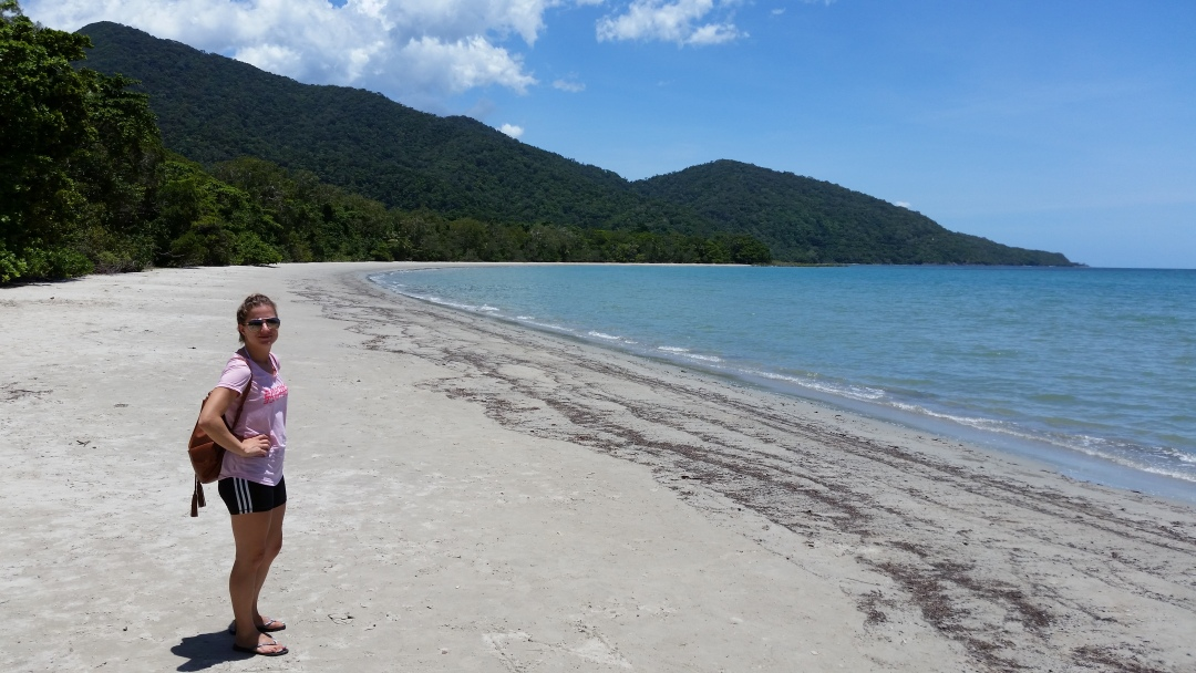 Standing on the beach at Cape Tribulation in Cairns where the rainforest meets the barrier reef