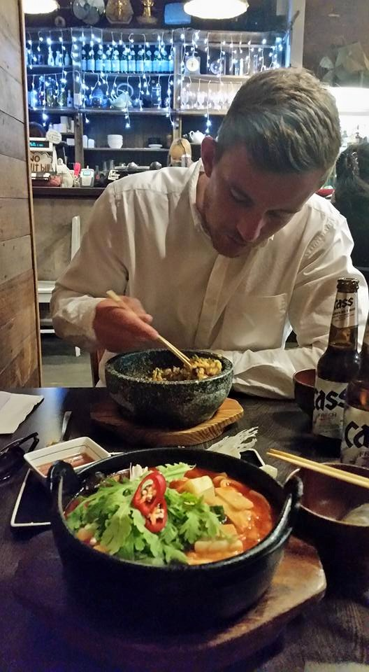 a guy eats his bibimbap while at a korean restaurant in melbourne