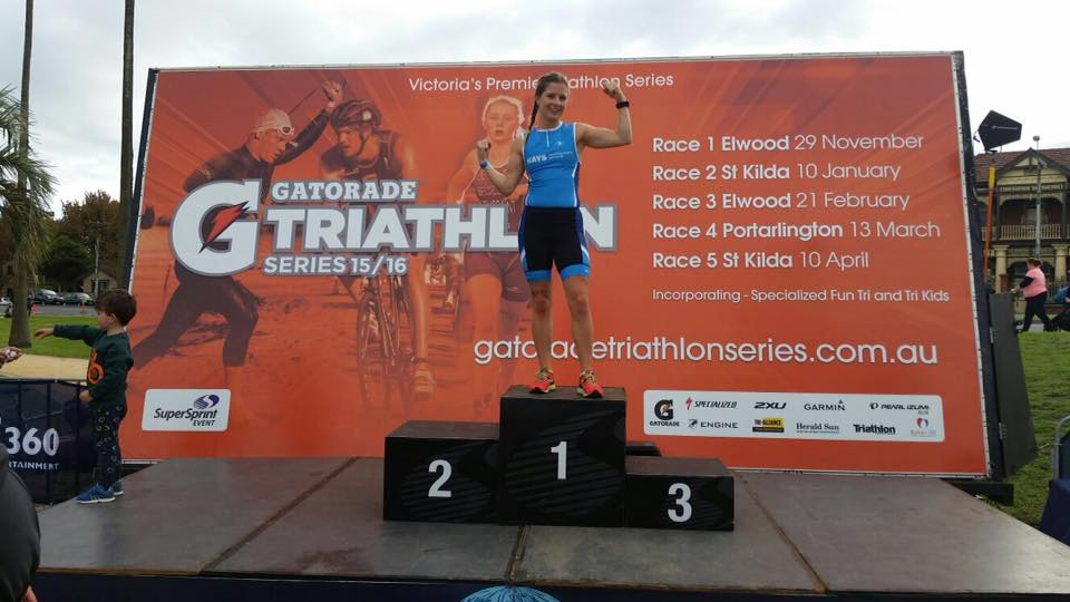 a woman standing on the podium after finishing her first triathlon event