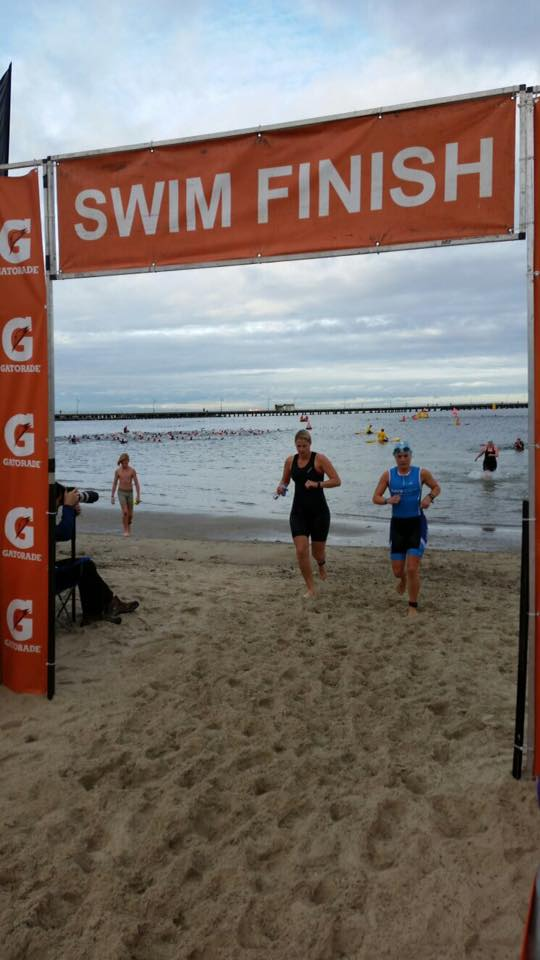 partakers of the gatorade triathlon in st kilda run onto the beach having completed the swim